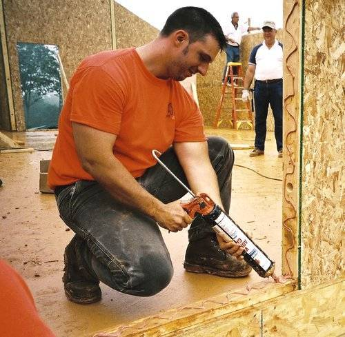 person building a small house kit putting caulk in window panel