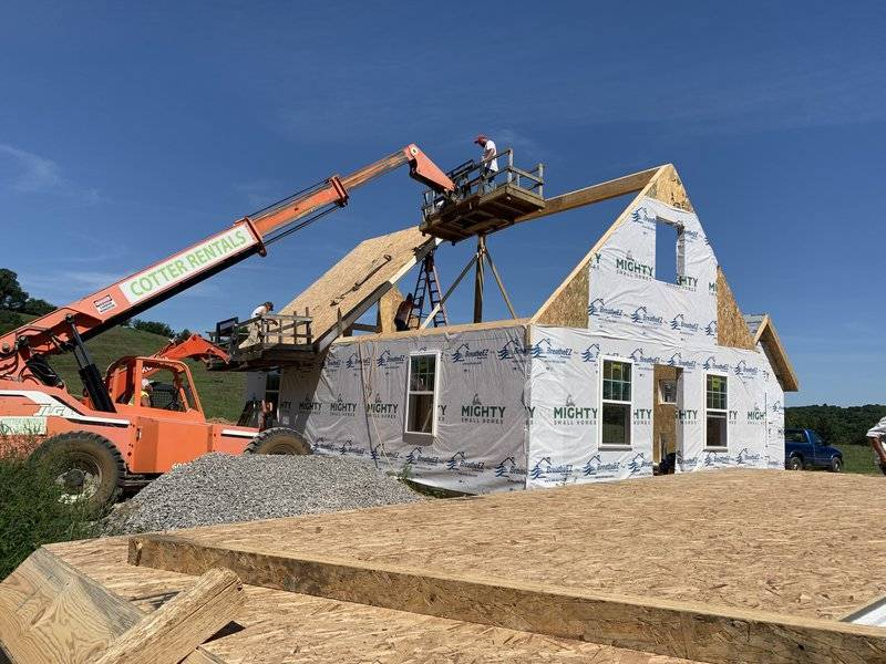 kit-home-construction-example-roof-panels-hydraulic-boom.JPGkit home construction site with roof panels lifted by hydraulic boom