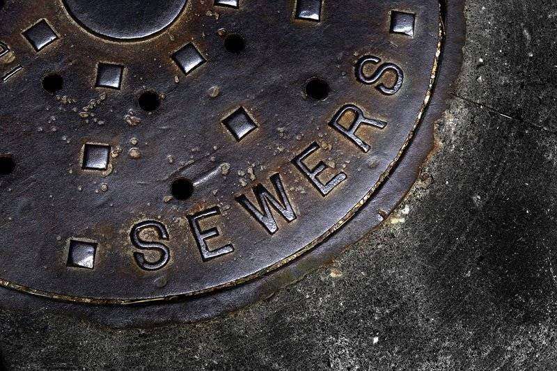 closeup photo of sewer manhole cover